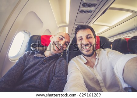 Happy couple taking selfie flying on the airplane - concept of friendship travel and holidays- Warm bright sunny afternoon color tones