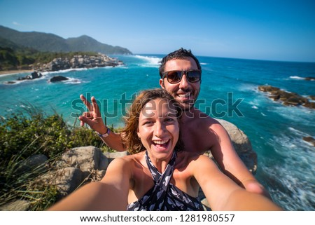 happy couple taking selfie photo in front of the sea in Tayrona National Park, Tropical Colombia