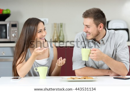 Happy couple talking sitting in the kitchen at breakfast #443531134