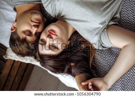 Happy couple. The husband hugs his pregnant beautiful wife, they spend time together on the bed in the bedroom #1056304790