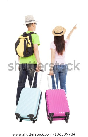 happy couple tourist with travel suitcase and pointing something - stock photo