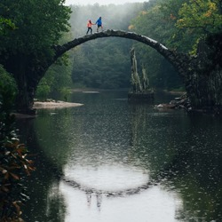 Happy couple traveling. Bridge in Kromlau, Saxony, Germany. Creative Artistic image.