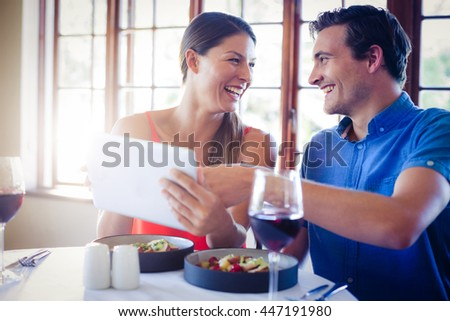 Happy couple using a digital tablet during lunch in restaurant #447191980
