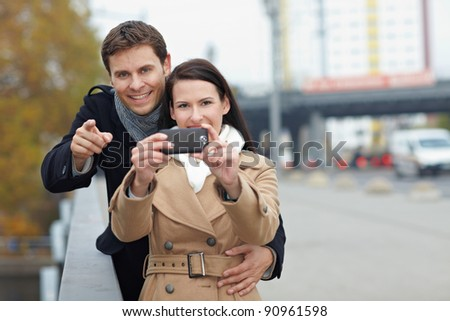 Happy couple using camera in mobile phone in a city