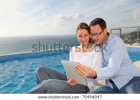 Happy couple using electronic tablet by swimming-pool