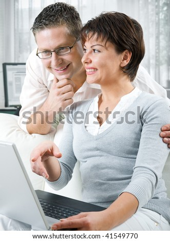 happy couple using laptop at home
