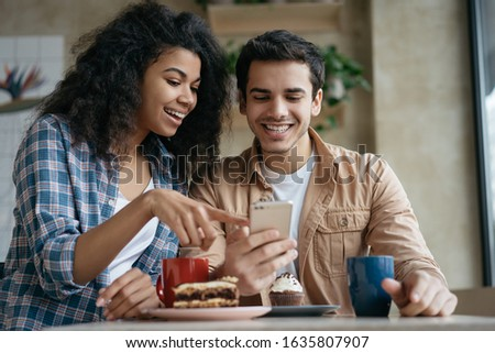 Happy couple using mobile phone application for online shopping. Emotional friends communication, laughing, looking at digital screen, sitting together in cafe