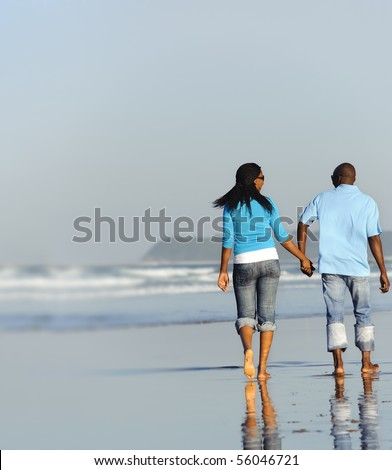 Happy couple walking on the beach in summer