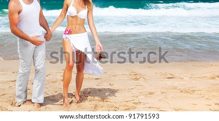 Happy couple walking on the beach, young new family spends honeymoon at tropical resort, holding hands, handsome man & beautiful woman in love, vacation & travel concept