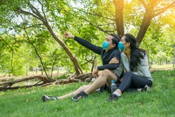 Happy couple wear athletic suits, wear masks and protect against Covid19 Disease and and talking together at park.Work out and Healthy and new normal concept.