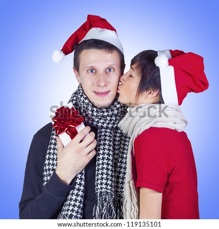 Happy couple wearing Santa hats and scarves celebrating Christmas.  Woman wearing Santa hat kissing man with Christmas gift box