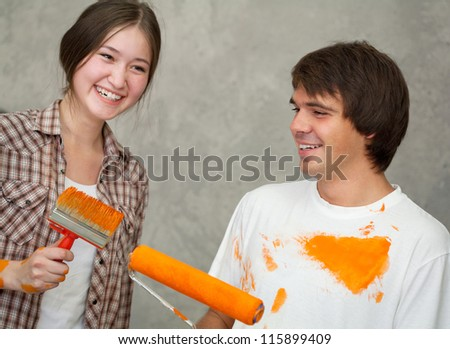 Happy couple while painting room