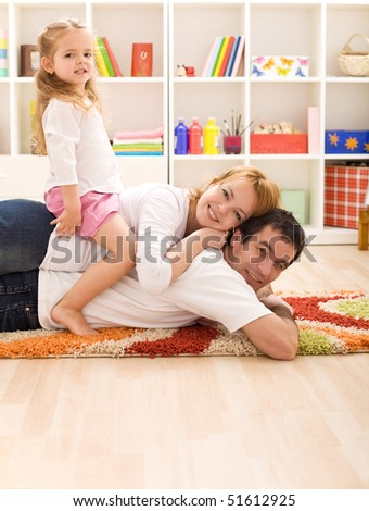 Happy couple with a child in the kids room having fun