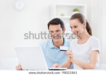 Happy couple with a credit card - stock photo