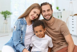 Happy couple with adopted African-American boy at home