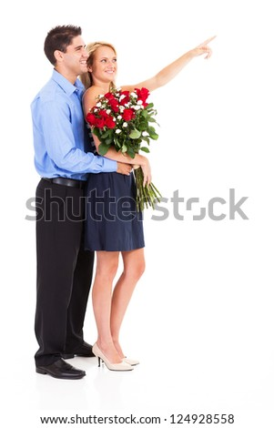 happy couple with bunch of roses isolated on white, woman is pointing