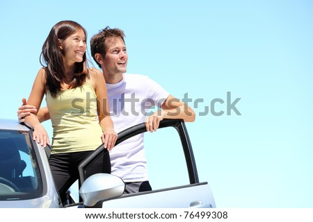 Happy couple with car. Young interracial couple standing with car looking at the sky with copy space.