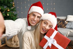 Happy couple with Christmas gift taking selfie at home