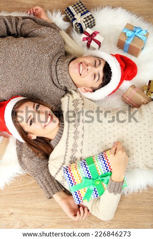 Happy couple with Christmas gifts relaxing at home