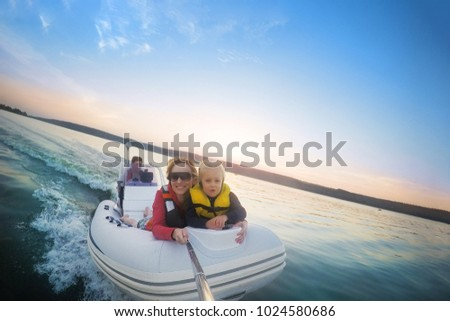 Happy couple with daughter riding boat on lake or river at sunset. Pair  with child making selfie while water activity.  Happy family  recreation and adventure concept. Beautiful travel background. #1024580686