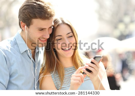 Happy couple with earphones sharing music from a smart phone on the street