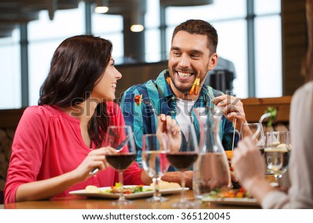 happy couple with friends eating at restaurant