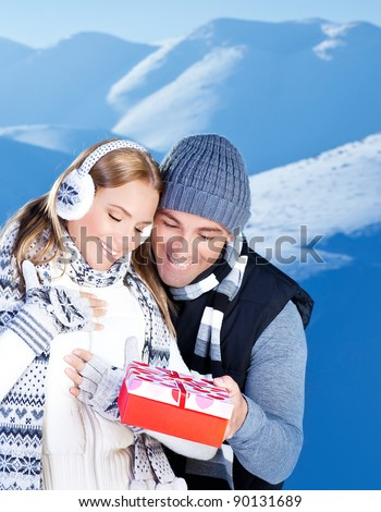 Happy couple with gift, people outdoor at winter snow mountains, young man giving present to beautiful woman, Christmas vacation holidays, love concept
