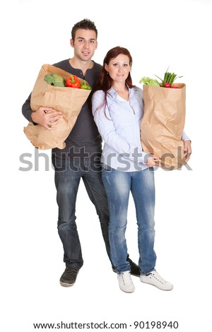 Happy couple with grocery shopping bags. Isolated on white
