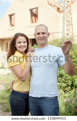 Happy couple with key against building new brick house