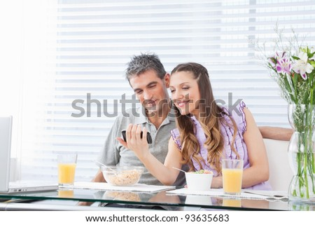Happy couple with laptop and smartphone at breakfast table - stock photo