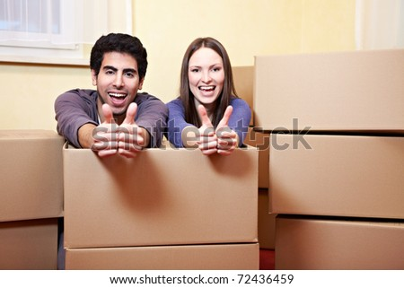 Happy couple with many moxing boxes showing their thumbs up