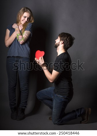 Happy couple with red heart on a dark background