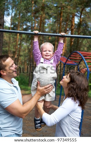 Happy couple with their little son  do exercises on the crossbar in the park - stock photo