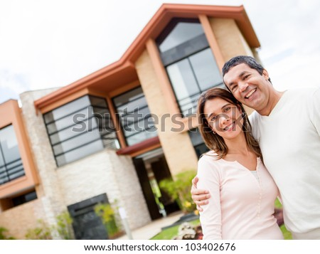 Happy couple with their new house at the background and smiling