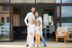 Happy couple with two kids standing on terrace of modern own house at background, happy parents with little children spending leisure time outside beautiful home looking at camera, family mortgage