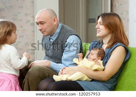 Happy couple with two their children  at home interior