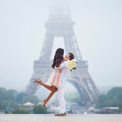 Happy couple with white roses near the Eiffel tower in Paris. Tourists enjoying their vacation in France. Romantic date or traveling couple concept
