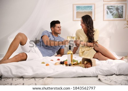 Happy couple with wine and tasty food imitating picnic at home Foto stock ©