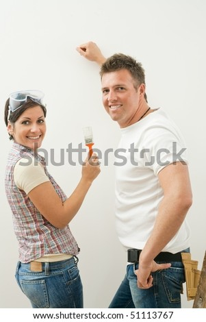 Happy couple working on improving home, painting wall, woman holding paint brush, looking at camera, smiling.