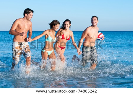 Happy couples of friends playing together and running in the water