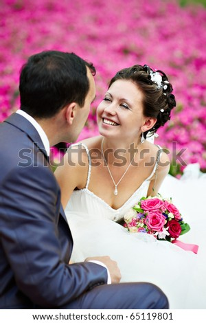 Happy couples on wedding walk on background of pink flowers - stock photo