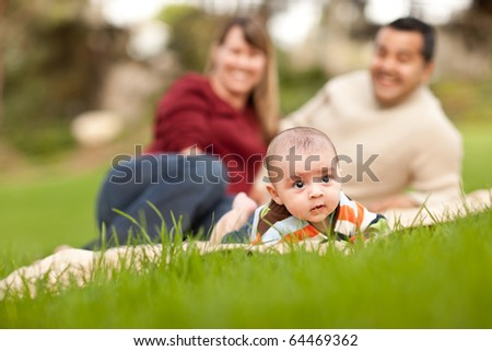 Happy Crawling Baby Boy and Mixed Race Parents Playing in the Park.