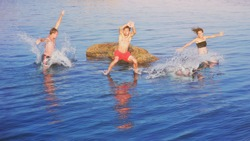 Happy crazy guys and girl jumping in natural sea pool from rock at sunset. Young fearless group of three friends fun diving in ocean water from cliff. Summer lifestyle and adventure vacation concept