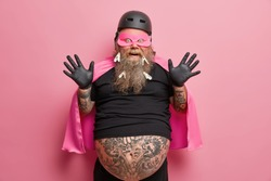 Happy crazy man has thick beard with clothespins raises hands in black rubber gloves has funny look plays with children on costume party wears superhero cloak mask and helmet isolated over pink wall