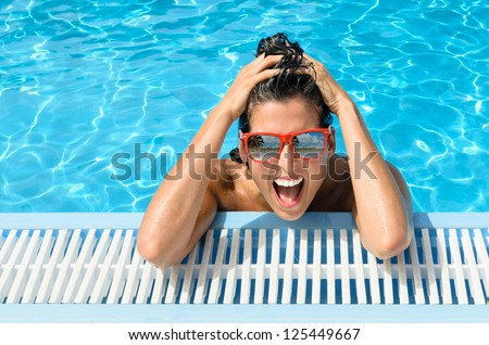 Happy crazy woman in resort pool on holidays. Funny happy girl face expression with red sunglasses on summer hot day. Reflection of beach and palms in glasses.