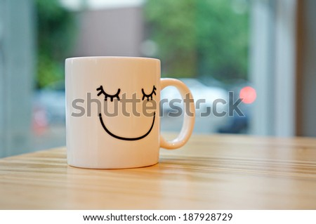 Happy cup on wood table with black polka dot tablecloth. Concept about happiness.