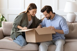 Happy curious couple unpacking parcel at home, sitting on couch, smiling woman looking into open cardboard box, satisfied clients customers received online store order, good delivery service