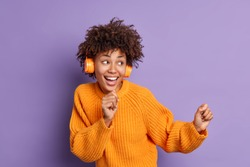 Happy curly haired fro American teenager dances carefree and sings favorite song listens music in headphones enjoys sound pleasant melody looks positively aside moves against purple background.