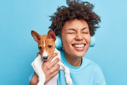 Happy curly haired teenage girl plays with pedigree dog enjoys company of favorite dog have walk together closes eyes wears stereo headphones listens music dressed casually isolated on blue background