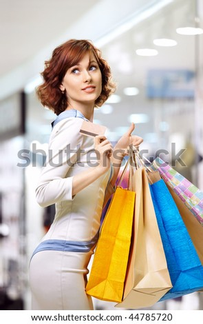 Happy curly woman on shopping with a credit card